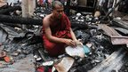 A Buddhist monk looks through burnt religious books at a torched temple