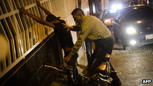 A police officer frisks a young man during a patrol of Petare, a neighbourhood of Caracas on 28 September 2012