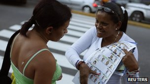 A supporter of Henrique Capriles shows a sample ballot to a woman