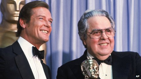 "Albert ""Cubby"" Broccoli, producer of the ""James Bond"" series, holds the Thalberg Award he received for his work at the Academy Awards, in Los Angeles. Roger Moore, left, British actor who plays secret agent 007 James Bond, made the presentation."