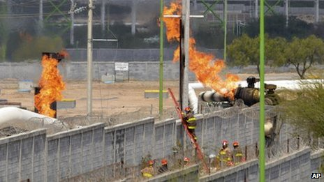Firefighter climb a ladder as they try to control a fire after an explosion at a gas pipeline distribution centre in Reynosa
