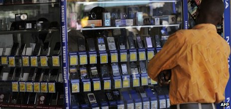 A man stands in front of a shop window displaying mobile phones on 1 October 2012 in Nairobi, Kenya