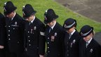 Police officers bow their heads as the funeral cortege of PC Fiona Bone passes