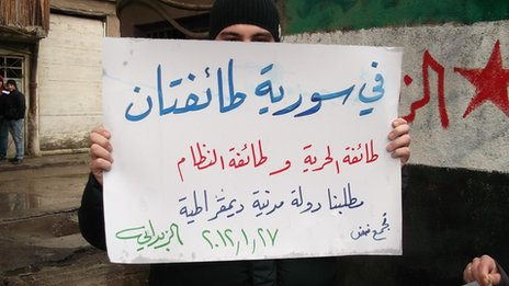 Syrian activist holding sign reading &quot;There are two sects in Syria - the sect of freedom and the sect of the regime&quot;