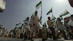 Members of India's landless holding green and white flags set off on a march to Delhi