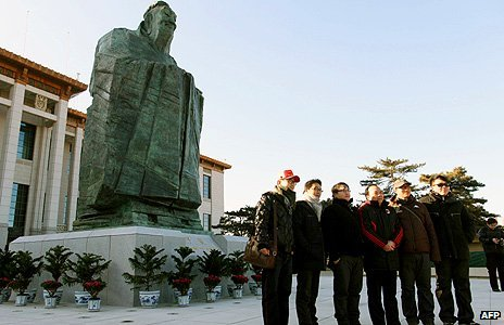 Chinese tourists pose in front of a statue of Confucius in Beijing's Tiananmen Square