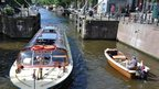 Tourist and local boats on an Amsterdam canal