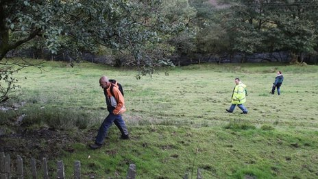 Volunteers search fields during the search for April