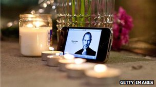 Candles and flowers placed outside Apple Store in New York