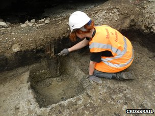 Archaeologist excavating a wooden stake thought to have been carved by a Bronze Age axe