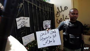 A Libyan security guard holds a slogan, which reads in Arabic &quot;Where is the security for us and for our guests&quot; at the main entrance of the US consulate in Benghazi on 18 September 2012