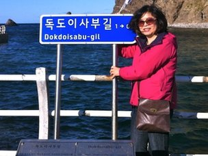 A South Korean tourist poses for a picture on the disputed Dokdo/Takeshima islands, 04 Oct 2012