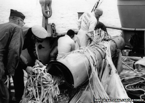 Navy personnel aboard USS Petrel examine weapon number 4, recovered from the sea bed and still tangled in its parachute
