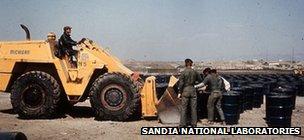 Air Force men loading dirt into barrels