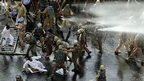 Indian policemen use batons and a water cannon to disperse Congress party workers