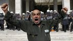 A shipyard worker shouts slogans in front of Greek Police headquarters