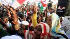 People waving flags outside Khartoum airport in Sudan - Friday 28 September 2012