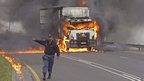 A policeman in front of a burning truck near Cape Town, South Africa - Wednesday 3 October 2012