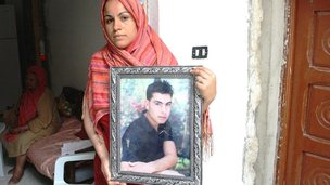 Tunisian Aida Dechich holds up a framed photograph of her brother Sofien Dechich