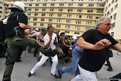 A riot policeman kicks out at protesters during a demonstration in the courtyard of the Defence Ministry in Athens