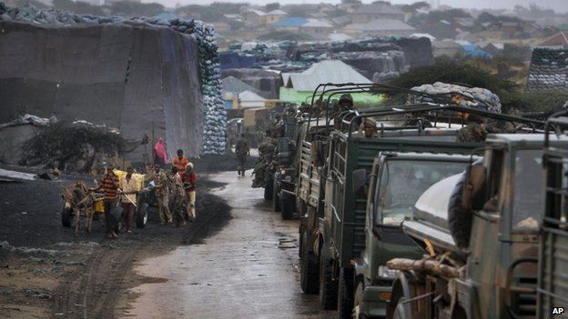Kenyan forces in Kismayo driving past charcoal sacks - the export of charcoal helped helped al-Shabab generate millions of dollars
