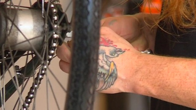 Tattooed hands working on bike wheel