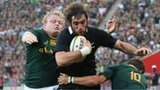 Sam Whitelock of the All Blacks moves past Johan Goosen and Adriaan Strauss to score a try