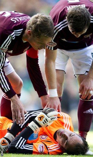 Marius Zaliukas and Darren Barr look concerned for Jamie MacDonald