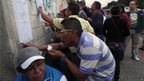 Residents of Caracas checking voter lists at a polling station (7 Oct)
