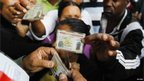 Voters showing their ID cards at a Caracas polling station (7 Oct)