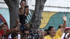 Chavez supporters cheer as their candidate arrives at a polling station in Caracas (7 Oct)
