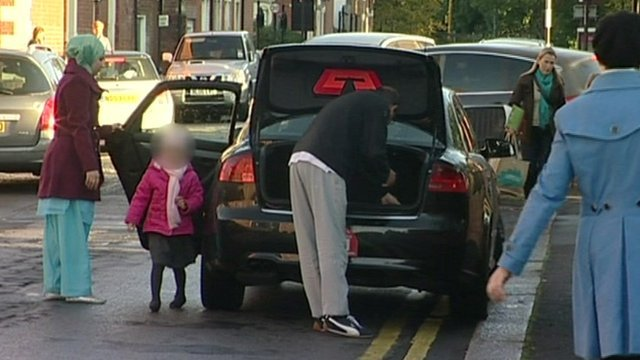 Family getting out of car parked on double yellow lines