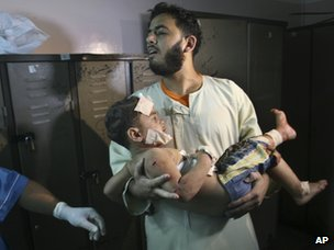A Palestinian man carries a boy injured in an Israeli air strike in Gaza (7 October 2012)