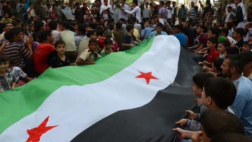 Protestors holding the Syrian flag