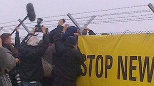 A protester scales the fence during a planned trespass at Hinkley Point