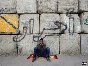"A protester rests next to a wall in Cairo's Tahrir Square bearing graffiti saying: ""Freedom"" (22 December 2011)"