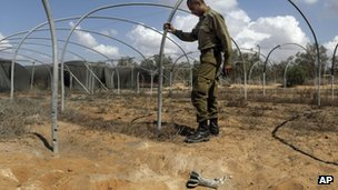 An Israeli soldier inspects a field where a mortar fell near the Israel-Gaza border (8 October 2012)