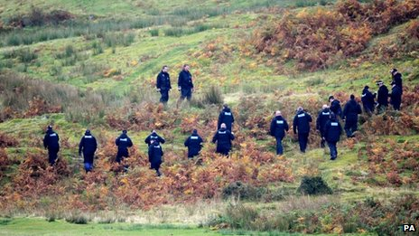 A police team search land near Machynlleth