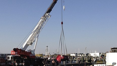 A crane lifts a car from the water in Newport