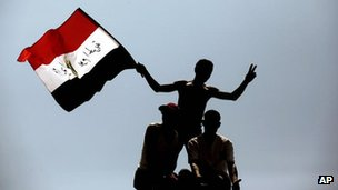 Protesters wave the Egyptian national flag as they perch on top of a street lamp in Tahrir Square in Cairo, Egypt (July 2011)