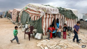 Syrian refugees in front of their makeshift tents at a refugee camp near the Syrian-Lebanese border