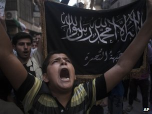 People hold up the flag of the al-Nusra Front at a protest in Aleppo (21 September 2012)