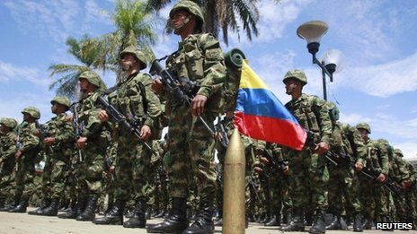 Colombian soldiers stand at attention next to their national flag during an inauguration ceremony for a new mobile brigade set up to fight the Farc, 5 October