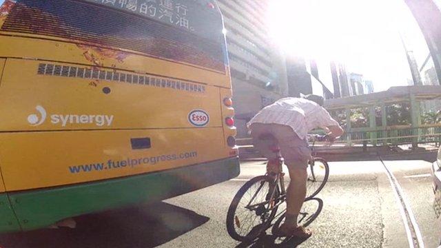 Man on bike behind bus in Hong Kong