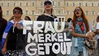 "Demonstrators display a banner reading ""Frau Merkel, get out"""
