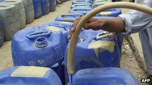 Man filling jerry cans with water