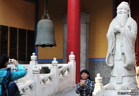 Woman mirroring the pose of Confucius outside the Confucius temple