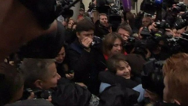Yekaterina Samutsevich in crowd of press and supporters