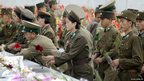 North Korean soldiers lay flowers in front of statues