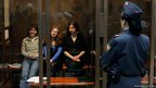 Members of the punk band Pussy Riot sit in a glass-walled cage before a court hearing in Moscow